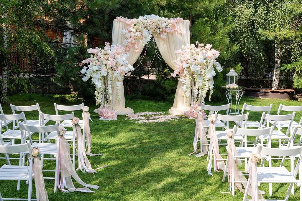Składane krzesła ślubne przygotowane do ceremonii w ogrodzie